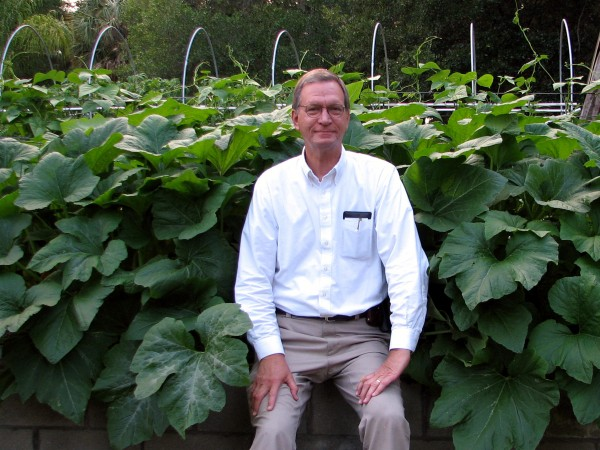 Stephen Clay McGehee in front of squash plants in raised bed garden.