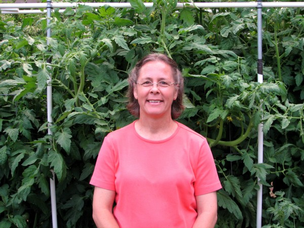 Laura McGehee in front of tomato plants in raised bed garden.